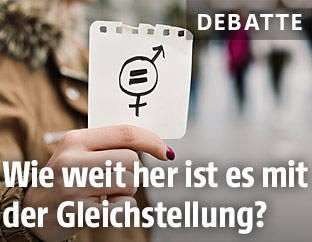 Eine Frau hält einen Zettel mit Gendersymbolen in der Hand