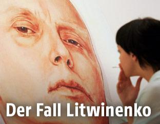Frau blickt auf ein an eine Hauswand gemaltes Porträt des russischen Agenten Alexander Litwinenko