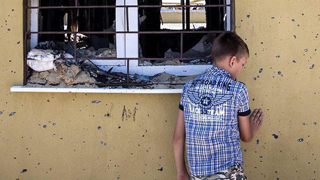 Ein Kind vor einer löchrigen Mauer