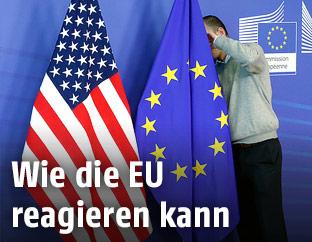 Arbeiter befestigt eine EU-Flagge neben einer USA-Flagge