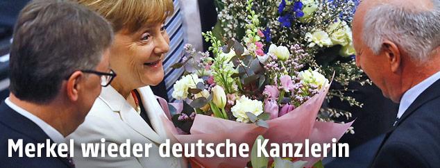 Die deutsche Bundeskanzlerin Angela Merkel mit Blumen