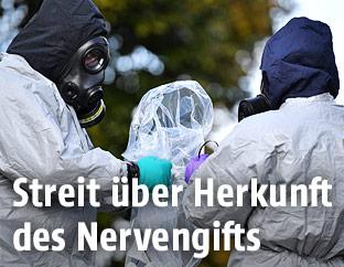Forensiker mit Schutzmasken entnehmen Proben