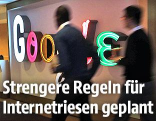 Männer im Anzug gehen an einem Google-Schild vorbei