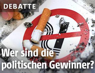 Ausgedämpfte Zigaretten auf Rauchverbotsschild