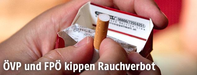 Eine Person nimmt eine Zigarette aus einer Zigarettenschachtel