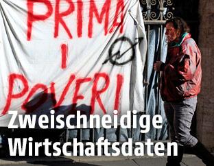 """Obdachlose Frau neben einem Banner mit der Aufschrift """"Prima i poveri"""" (Überseztung:  Die Armen zuerst)"""