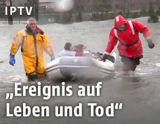 Eine Person wird von zwei Feuerwehrleuten aus den Fluten gerettet