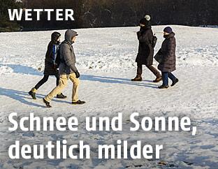 Menschen gehen im Schnee bei Sonnenschein spazieren