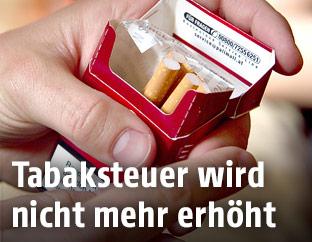 Zigarettenpackung in der Hand eines Mannes