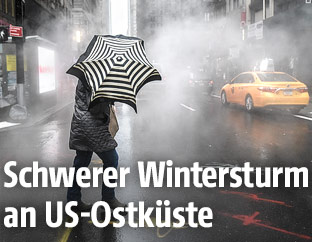 Mann kämpft sich mit Regenschirm durch die Straßen von New York