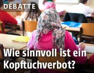 Mädchen mit Kopftuch sitzt in einer Schulklasse