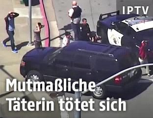 Personen mit Händen hinter dem Kopf gehen an Polizisten vorbei