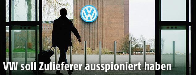 Ein Mann mit einem Trolley verlässt ein Gebäude gegenüber dem VW-Werk in Wolfsburg