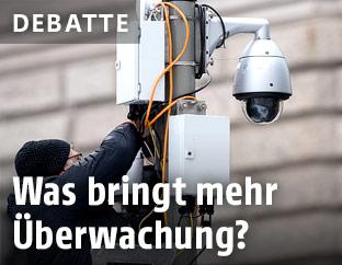 Ein Techniker hantiert an einer Überwachungskamera
