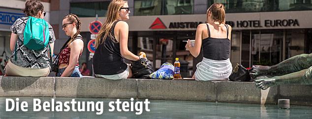 Frauen sitzen in der Sommerhitze bei einem Brunnen