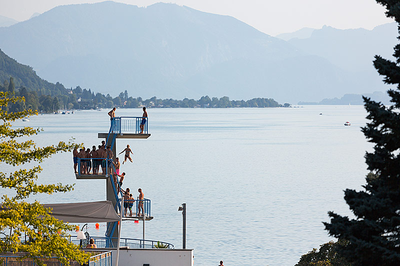 Badeggäste springen vom Sprungturm des Strandbad Seewalchen am Attersee