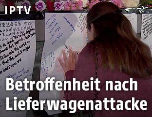 Frau schreibt auf eine Gedenkwand