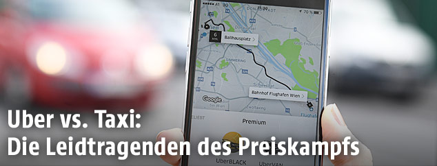 Uber-App auf einem Smartphone mit Autos im Hintergrund