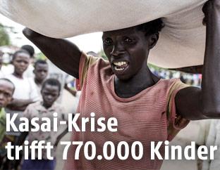 Frau in der Kasai-Provinz trägt Nahrungsspende, im Hintergrund kinder