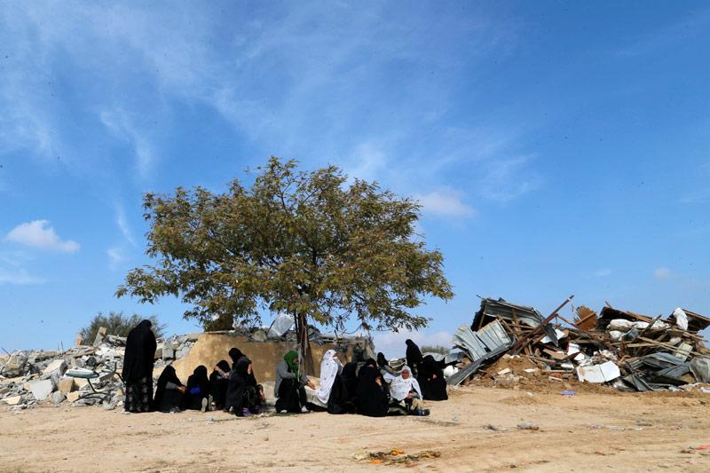 Arabische Frauen vor einem zerstörten Haus