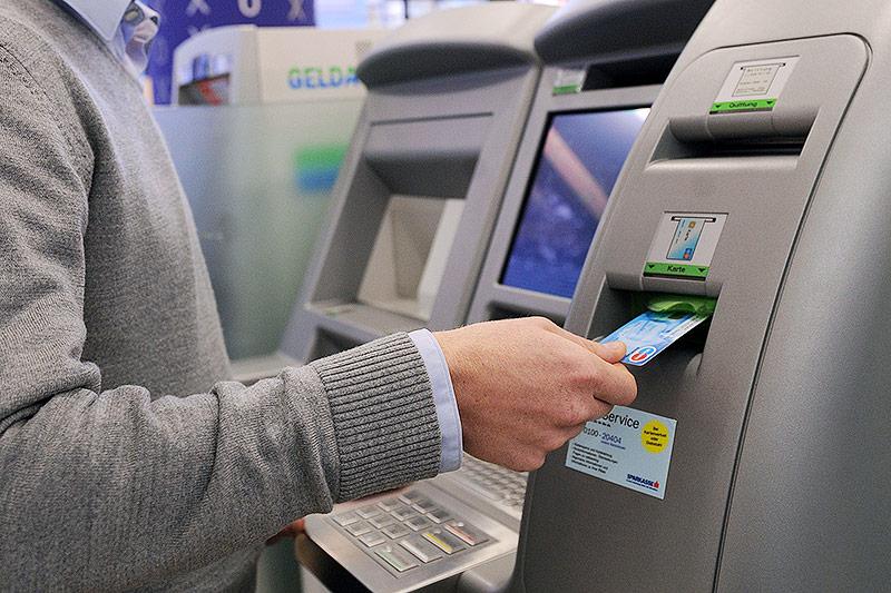 Mann steht am Bankomat