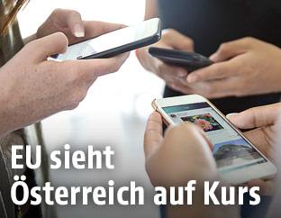 Drei Personen halten Smartphones in den Händen