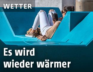 Frau sonnt sih im Wiener Museumsquartier auf einem Enzi