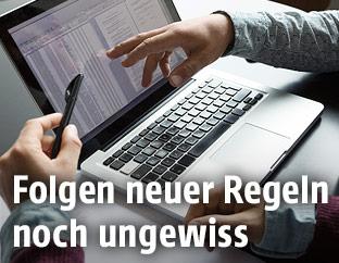 Menschen deuten auf Laptopbildschirm