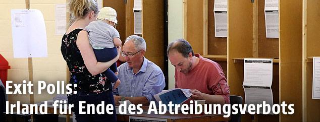 Eine junge Frau mit einem Baby am Arm in einem Wahllokal bei der Abstimmung