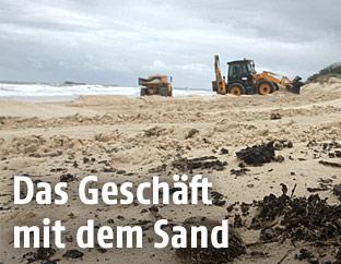 Ein Bagger trägt Sand an einem Strand ab