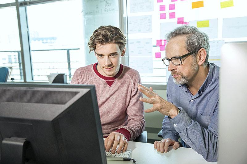 Ein Mann mit grauem Bart schult einen jungen männlichen Praktikanten vor einem PC-Monitor ein
