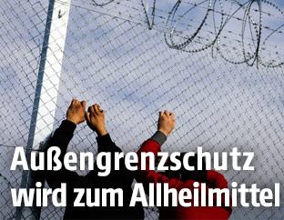 Flüchtlinge an einem Grenzzaun