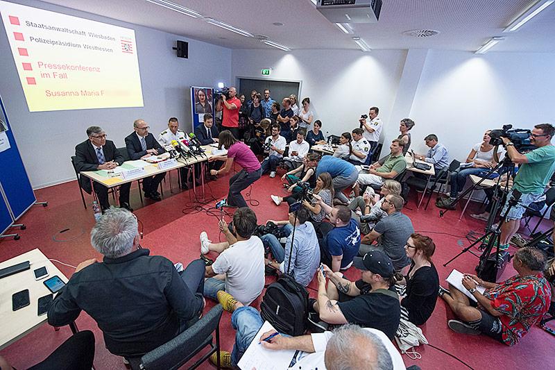 Journalisten fotografieren bei einer Pressekonferenz ein Foto des Verdächtigen