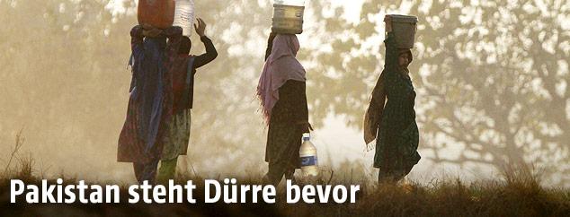 Frauen tragen Wasserbehälter