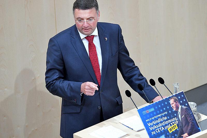 Der Abgeordnete Jörg Leichtfried (SPÖ), vor ihm ein Bild mit der FPÖ-Aufforderung für eine verbindliche Volksabstimmung zu CETA und TTIP