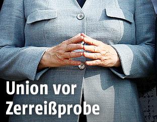 Angela Merkels macht eine Raute mit ihren Händen