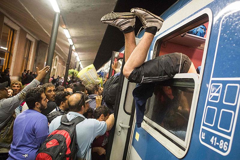 Flüchtlinge versuchen verzweifelt, einen Zug von Györ nach Hegyeshalom zu besteigen