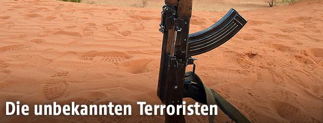 Eine Kalaschnikow AK-47 steht im Wüstensand