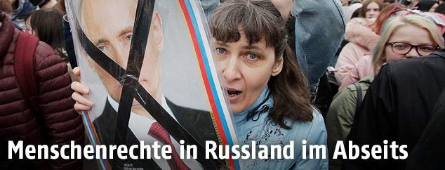 Demonstranten mit einem durchgestrichenen Putin-Plakat