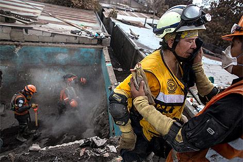 Einsatzkräfte auf der Suche nach Überlebenden nach dem Ausbruch des Feuervulkans in Guatemala