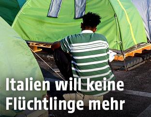 Ein Asylwerber sitzt zwischen Zelten