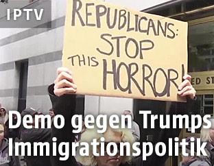Demonstranten halten ein Schild gegen Trumps Politik ein die Höhe