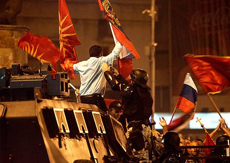 Demonstrant auf einem Polizeifahrzeug