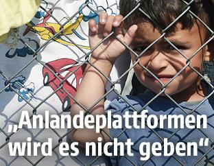 Kind hinter einem Zaun