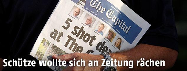 """Ein Sheriff hält am Tag nach der Tat die Zeitung """"The Capital"""" in der Hand"""