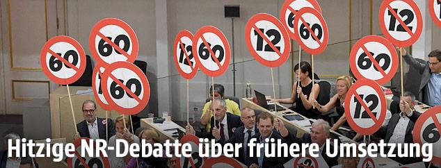 SPÖ-Abgeordnete halten Schilder mit einer durchgestrichenen 12