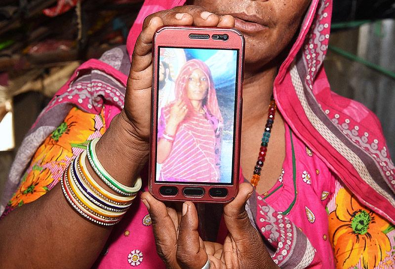 Frau hält ein Foto ihrer Cousine auf einem Smartphone in die Kamera