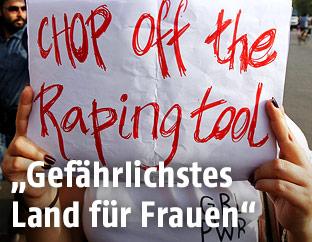 "Frau hält Schild mit der Aufschrift ""Chop off the raping tool"""