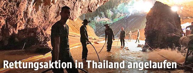 Thailändische Soldaten mit Schläuchen in einer Höhle