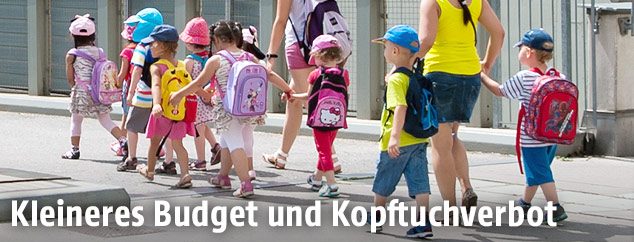 Kindergartenkinder überqueren mit Betreuerin eine Straße